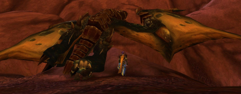 A paladin stands over the body of a slain drake.